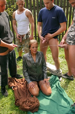 Fully clothed blonde in stockings getting pissed on in outdoor fetish gangbang
