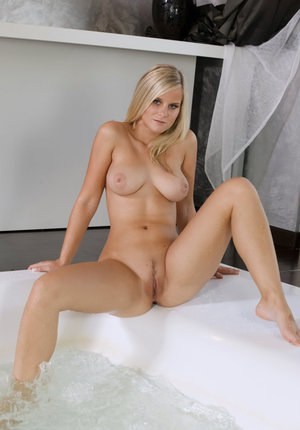 Busty blonde bombshell Miela A spreading legs in bath to show wet pussy