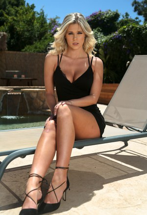 Blonde pornstar sheds short black dress to pose naked outdoors
