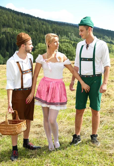 Young Swiss homemaker in pigtails kneels in a field to enchant two tough manhoods
