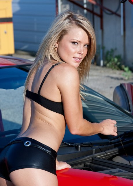 Blond-haired amateurish Slake Madden poses in gas-tight shorts and brassiere on a sports car