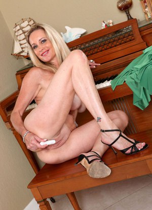 Classy mature woman Cassy Torri toys her vagina after removing her dress