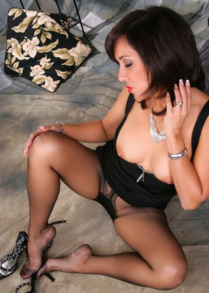 Mature housewife in black dress removes her heels from hose covered feet