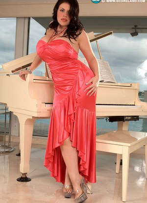 Curvaceous solo model with fair skin takes off her long dress on piano bench