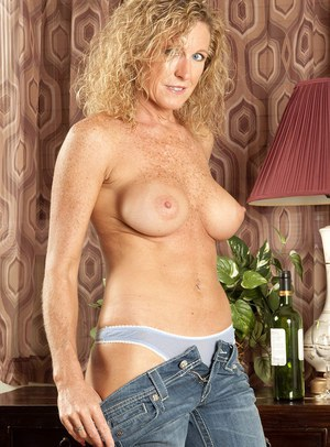 Blonde mature with nice tits slips off her jeans and poses topless in undies