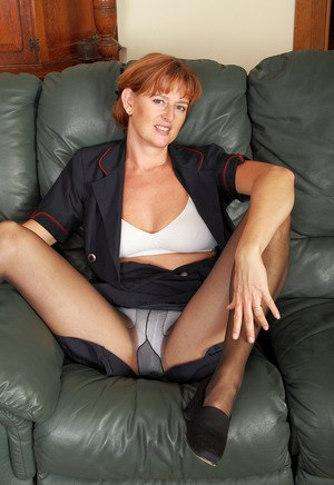 Horny mature Liddy sheds flight uniform to lounge naked  spread pussy lips
