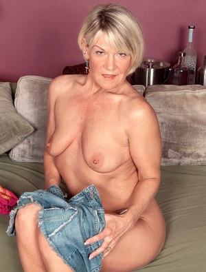 Middle-aged lady with blonde hair flashes upskirt panties before undressing