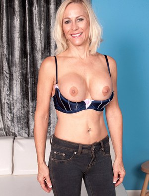 Middle aged blonde fondles her round breasts as she takes off her clothes