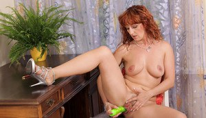 Older woman with red hair toys her pussy after getting undressed