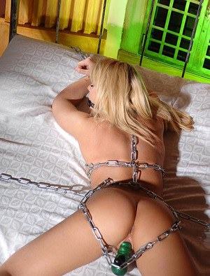 Naked blonde Zorah White is left chained and ballgagged on white bed sheets