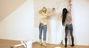 2 clothed woman laying wallpaper cover each other in slimy paste
