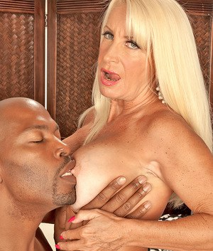 Big boobed cougar in stockings Merilyn feeds herself with a black shaft