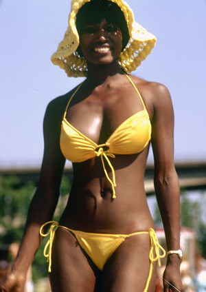 Black female in sunhat and bikini heads into the bushes to pose naked