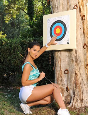 Fit brunette archer Eve Angel removes her sexy shorts to shoot naked outdoors