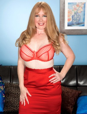 Mature solo girl Heather Barron frees her big tits from red lingerie in nylons