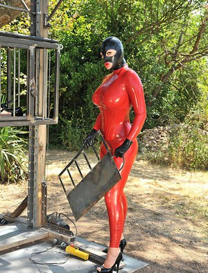 Masked stacked fetish models in latex catsuits playing rough games outdoors