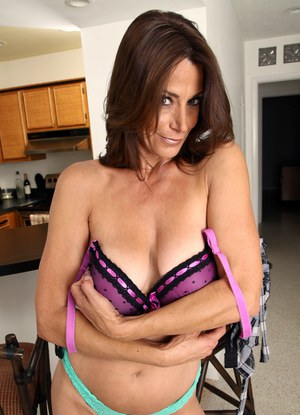 Middle-aged woman undresses prior to masturbating on kitchen counter