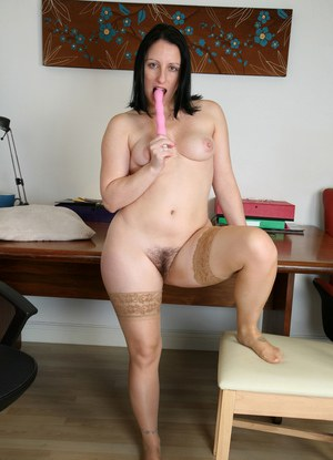 Middle aged woman with dark hair pleasures herself in tan stockings