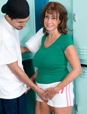 Hot granny Jacqueline Jolie seduces a young guy in locker room wearing shorts