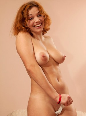 Redhead amateur Peach uncovers her firm breasts as she undresses