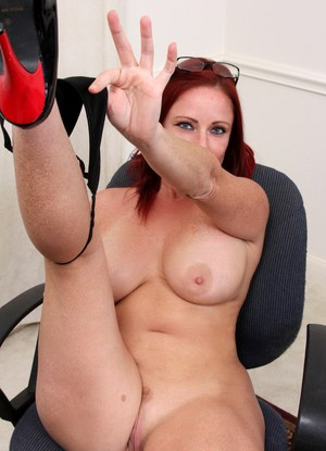 Redhead secretary uncovers her large boobs and ass as she strips on her desk