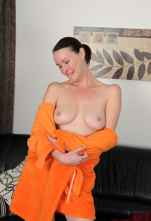 30 plus female Veronica Snow pets her trimmed bush while doing her laundry
