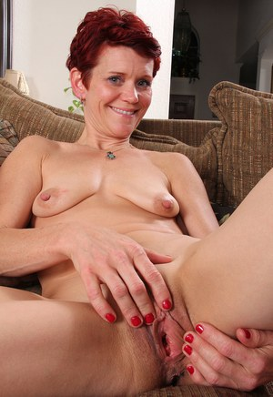 Aged redhead Suzy Stanton takes off lingerie to pet her bald pussy on sofa