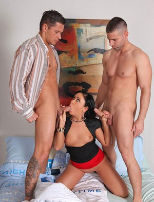 Clothed brunette undresses and gives two cocks blowjobs in threesome
