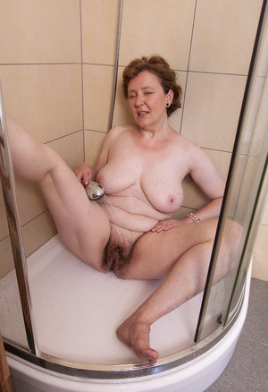 Mature fatty Romana Sweet shows off unshaven armpits and beaver in bathroom