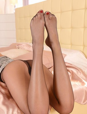 Solo girl Nicole Smith rolling pantyhose down long sexy legs