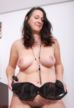 Over-30 lady with black hair proudly displays her beaver after stripping naked
