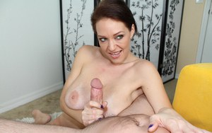 Busty female Charlee Chase undresses prior to giving a handjob