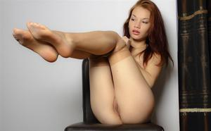 Young redhead takes off her hose and shows the pink of her snatch
