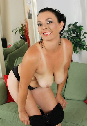 30 plus brunette Leona Sweet uncovers her big naturals as she undresses