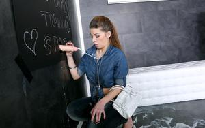 Clothed girl pulls down her jeans while getting doused with gloryhole jizz