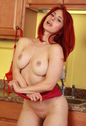 Slutty redhead housewife Andrea Rosu has fun pleasuring herself in the kitchen