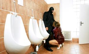 Clothed female is sexually assaulted by masked man in corporate bathroom