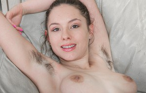 Solo model with a pretty face shows off her unshaven armpits and vagina