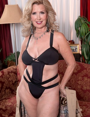Older blonde Laura Layne flashes her sexy lingerie ensemble before baring tits