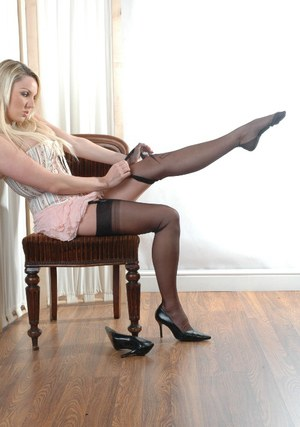 Blonde with long hair Dannii Harwood rolls on her nylons and affixes garters