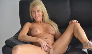Older blonde lady Erica Lauren strokes her pussy after getting naked