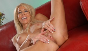 Older blonde lady Erica Lauren displays her pink pussy on a leather sofa