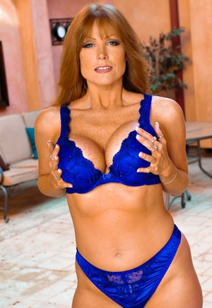 Older redhead Darla Crane kisses a young stud while seducing him in lingerie