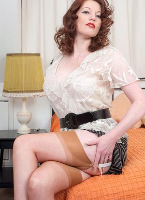 Redhead MILF Holly Kiss strips to girdle and tan nylons before toying her cunt