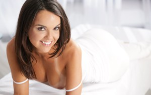 Smiley brunette slips out of her white suit to pose seductively on the bed