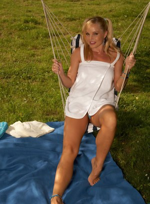 Top MILF pornstar Silvia Saint stripping naked in pigtails on grassy lawn