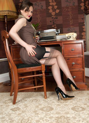Hot secretary Tina Kay in vintage lingerie poses at her office desk topless