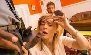 Older redhead Nina Hartley seduces and fucks a young black stud in her office