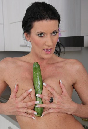 Hot brunette MILF toying bald beaver with cucumber close up in the kitchen