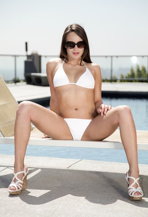 Erotic brunette Teal Conrad lounges naked to spread legs by the pool